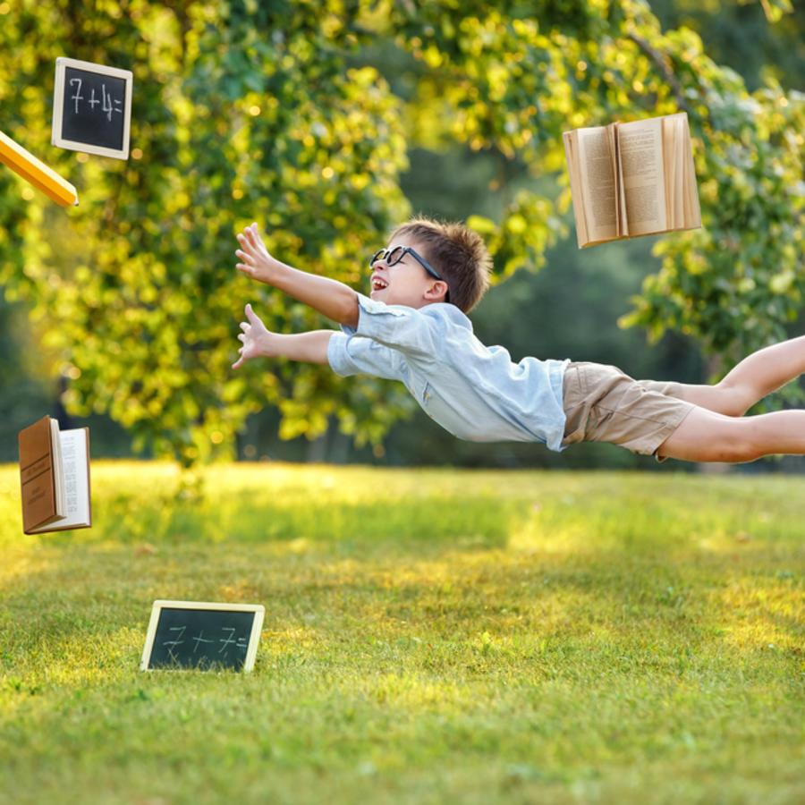 Niño volando con tareas escolares