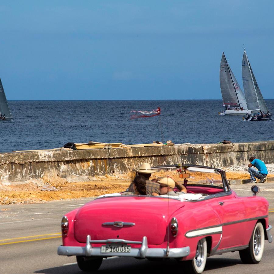 Veleros de Estados Unidos participan en una competencia mientras turistas recorren el Malecón de La Habana en un convertible clásico el miércoles 3 de febrero de 2016.