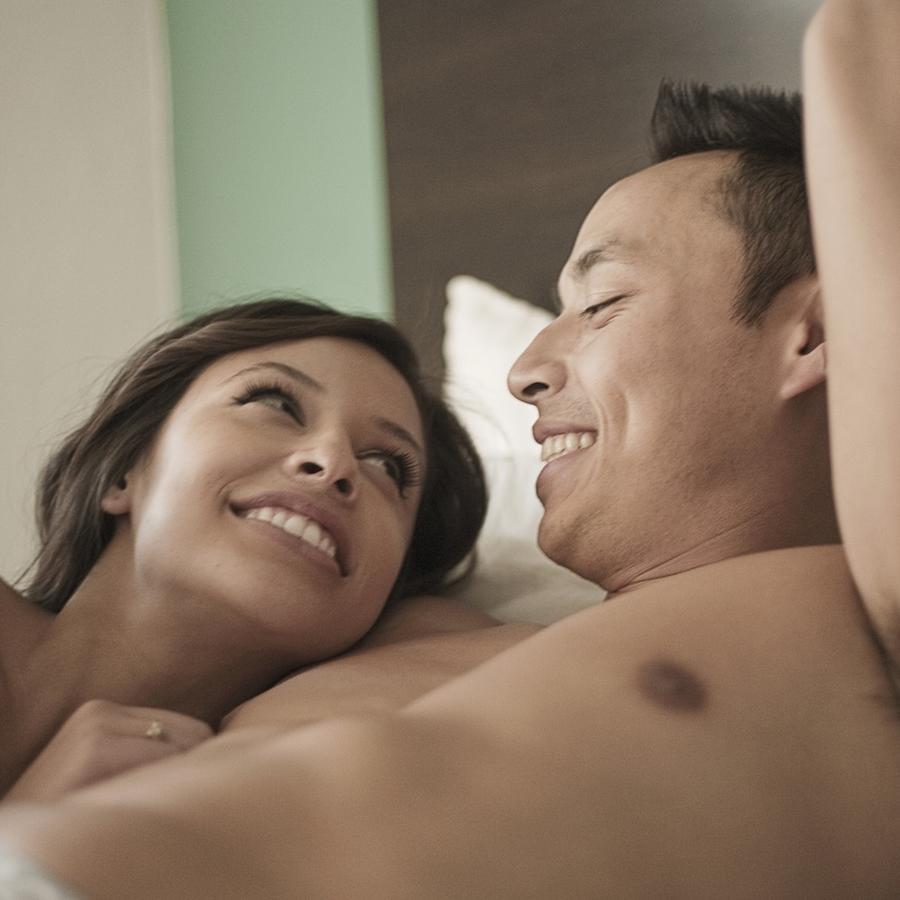 Pareja abrazada sonriendo en la cama