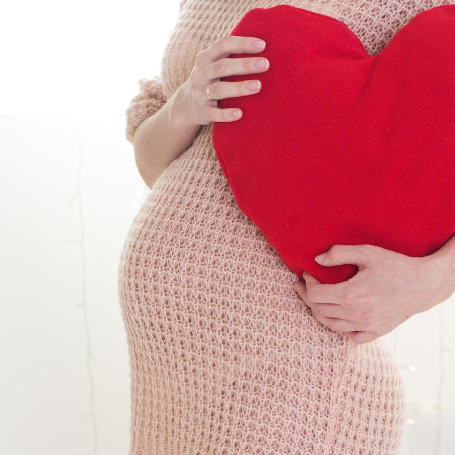Mujer embarazada sosteniendo cojín en forma de corazón