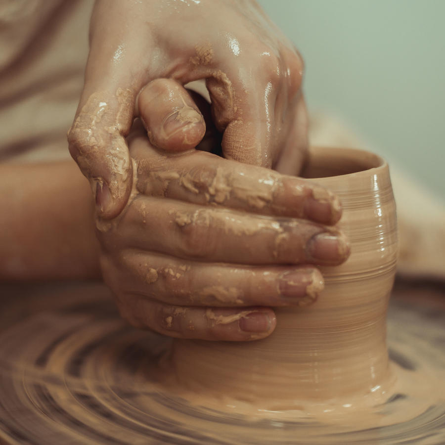 Manos de hombre trabajando pieza de cerámica en rueda de alfarería