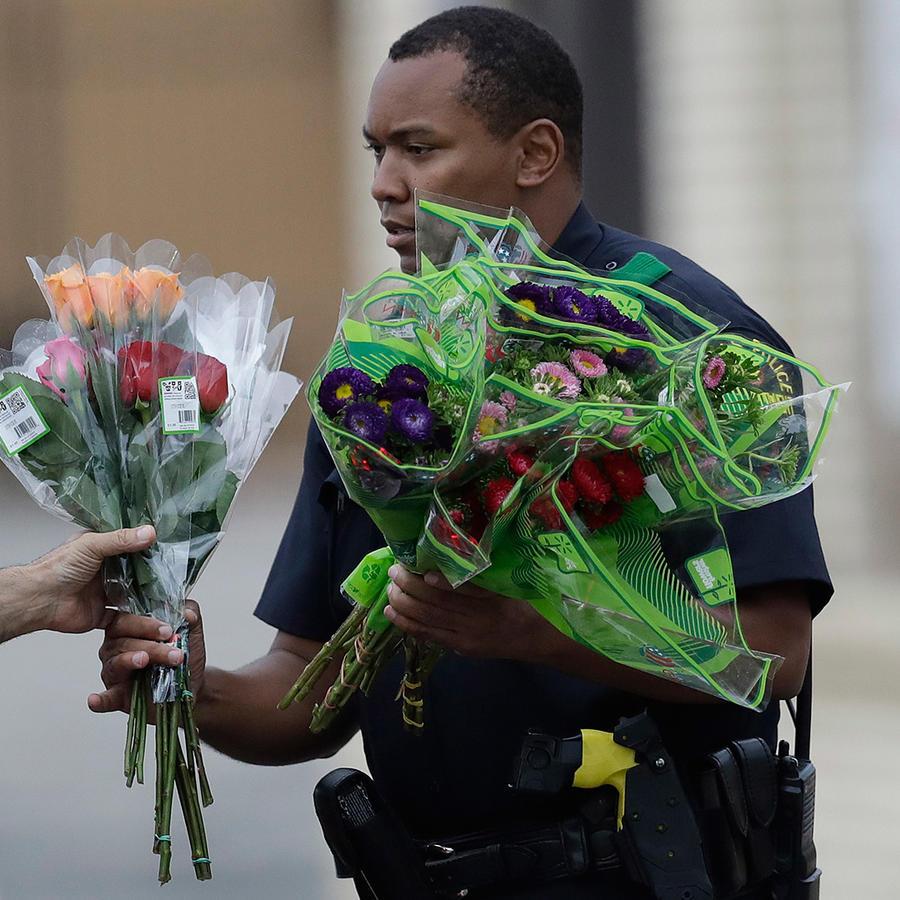 Un agente de policía de Dallas recibe flores en un retén frente a su cuartel, 9 de julio de 2016.