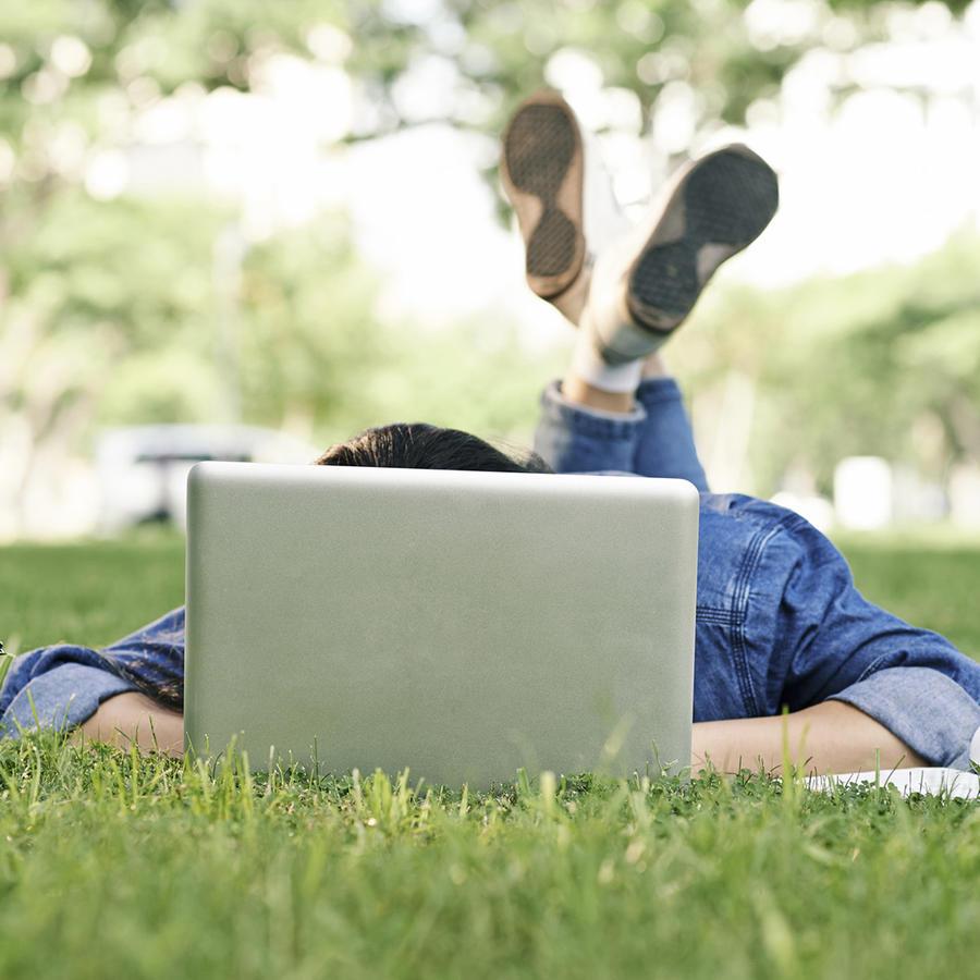Estudiante con computadora en el pasto