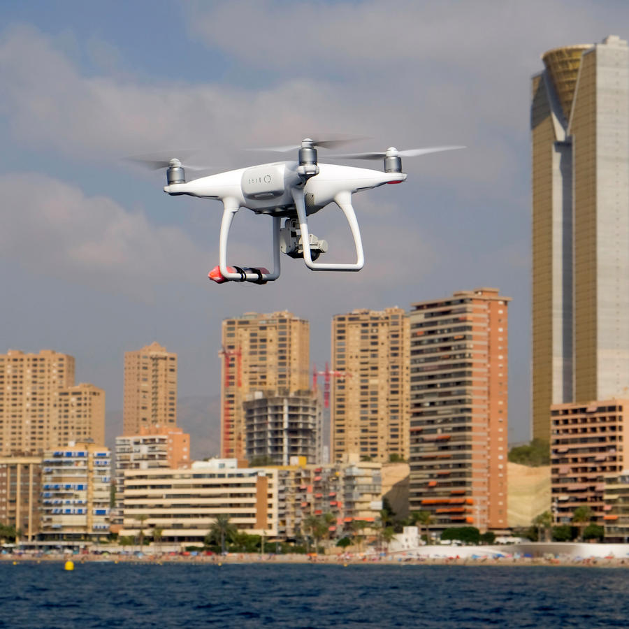 A drone, equipped with a camera used by police for surveillance tasks, flies in front of Poniente beach in Benidorm