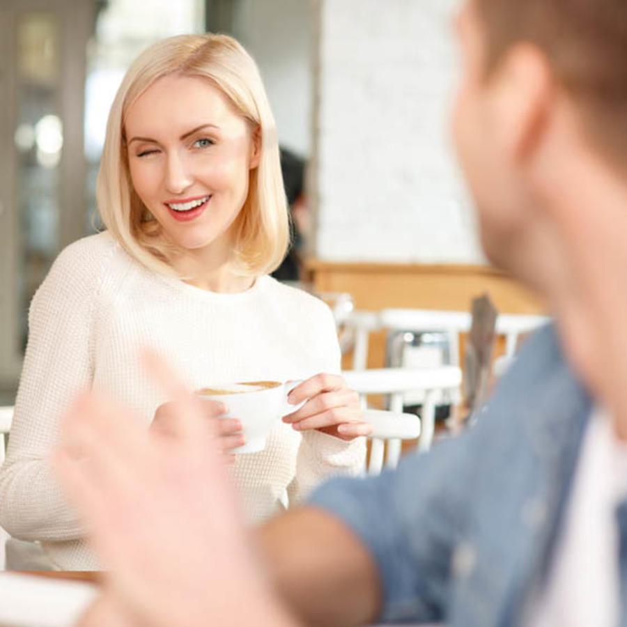 Chica coqueteando con chico en un café
