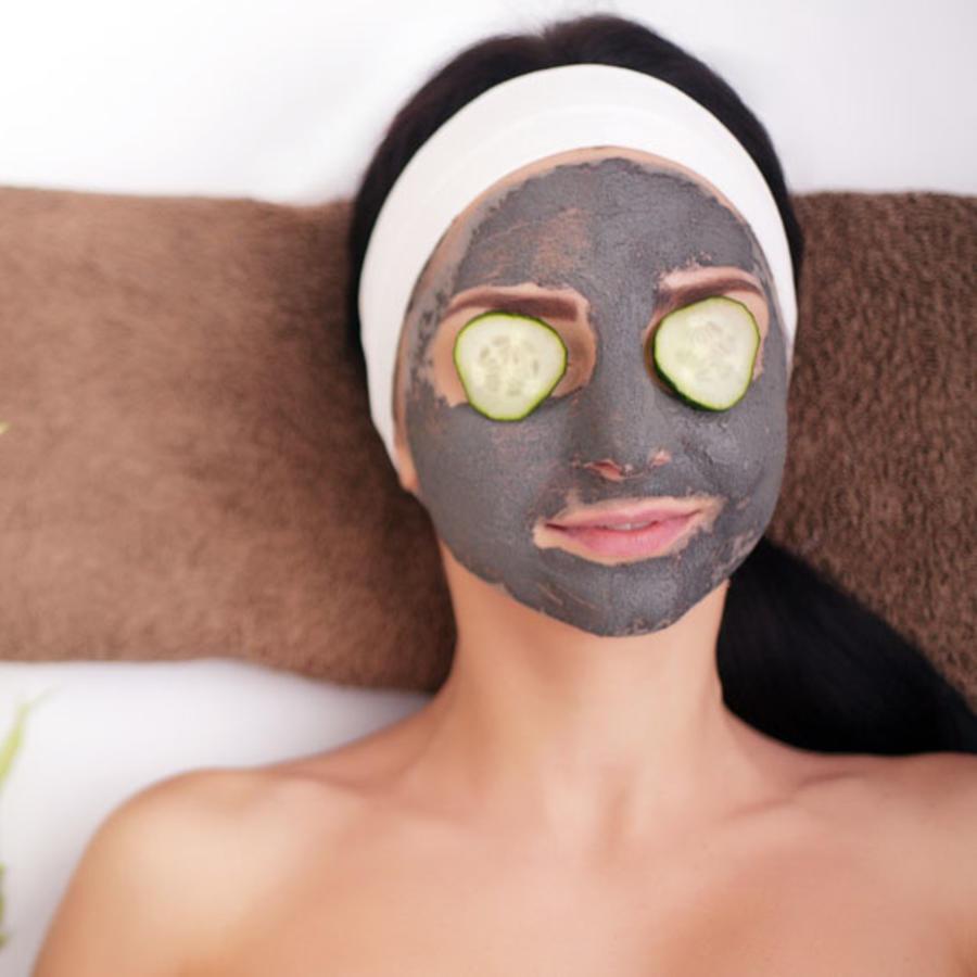 Mujer con mascarilla de barro  en la cara y pepinos en los ojos