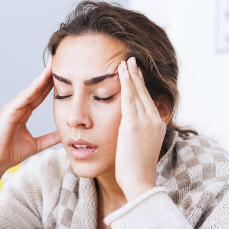 Mujer llevándose las manos a las sienes por el dolor de cabeza