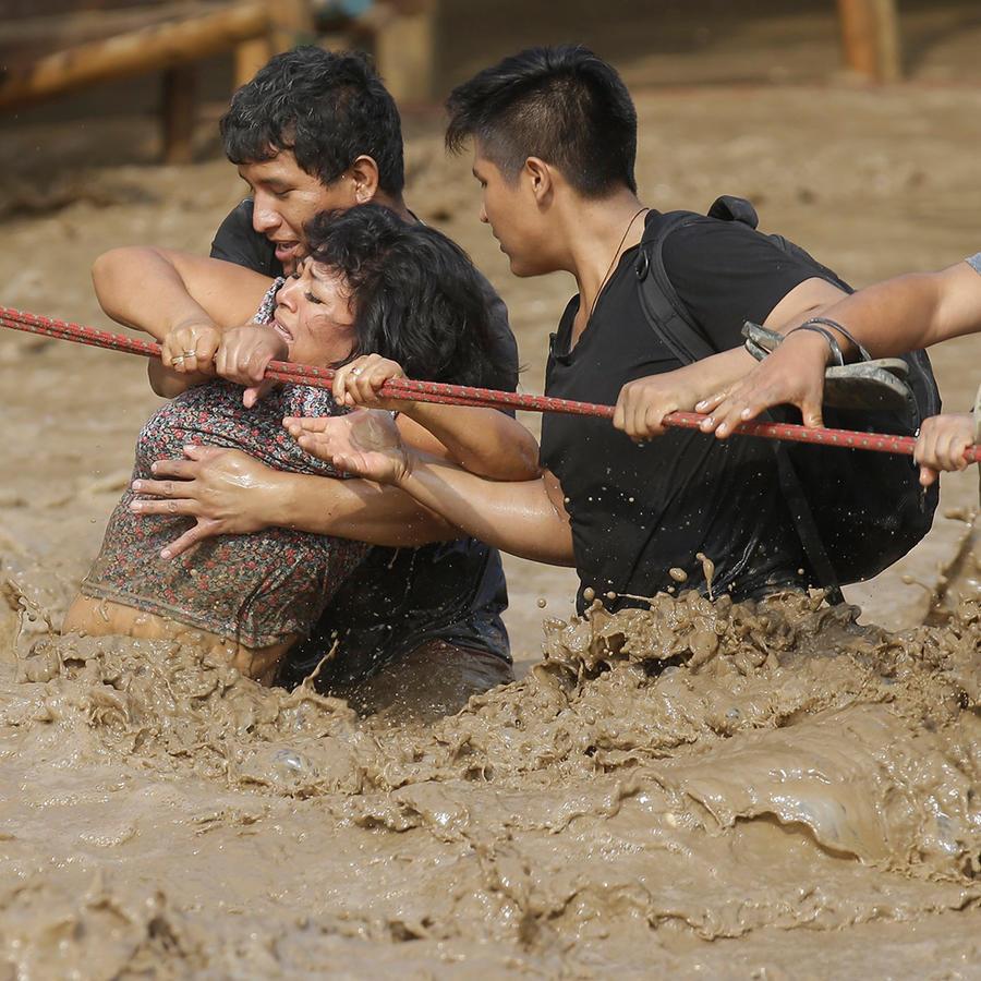 Un grupo de personas, atrapados en las aguas de las inundaciones, se aferra a una cuerda en Lima, Perú, el viernes 17 de marzo de 2017.