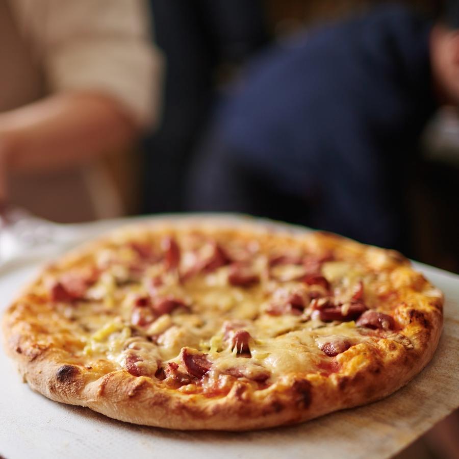 Cocinero con pizza recién salida del horno