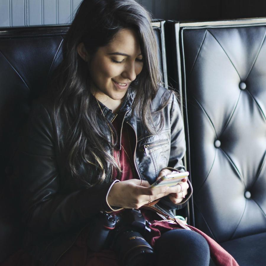 Chica enviando mensajes desde un sofá