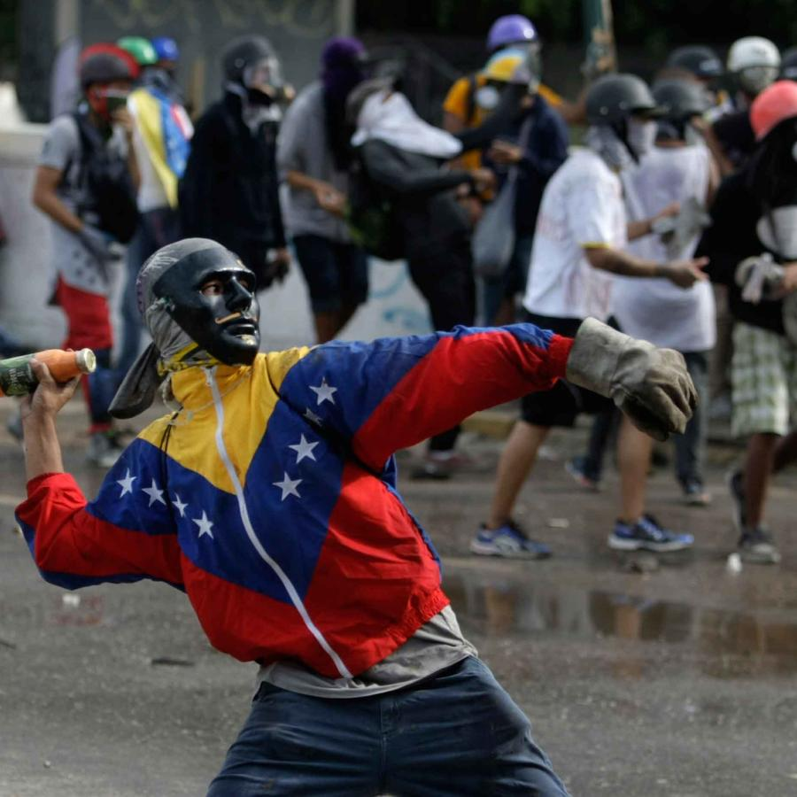 Un manifestante lanza objetos durante marcha en Caracas