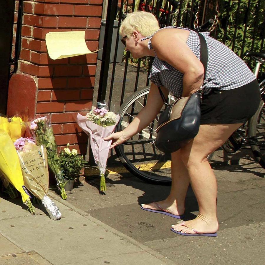 Una mujer deposita un ramo de flores cerca de la mezquita londinense de Finsbury Park, donde un conductor lanzó su vehículo a medianoche contra las personas que salían del templo y causó un muerto y diez heridos.