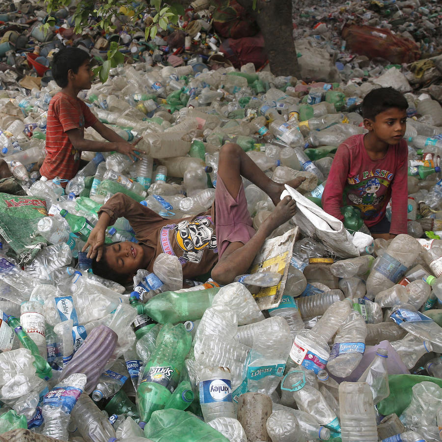 Niños en India sobre un montón de botellas de plástico el pasado abril.