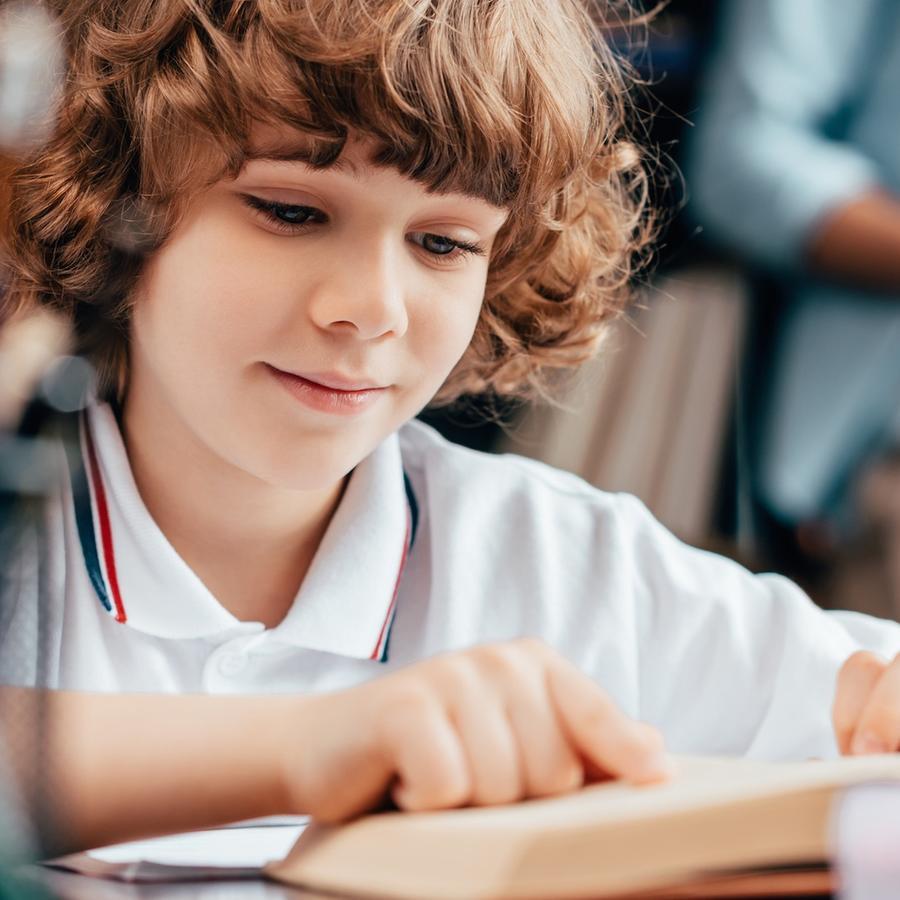 Niño con uniforme escolar aprendiendo a leer