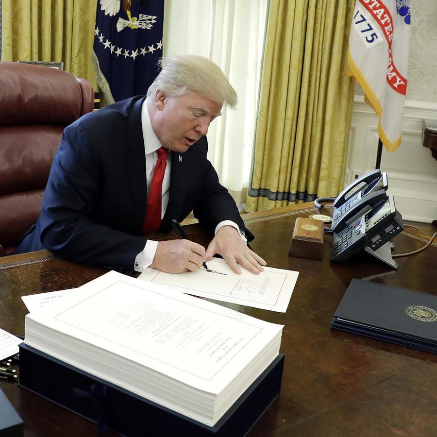 El presidente Donald Trump firma la reforma tributaria en la Oficina Oval el viernes 22 de diciembre del 2017