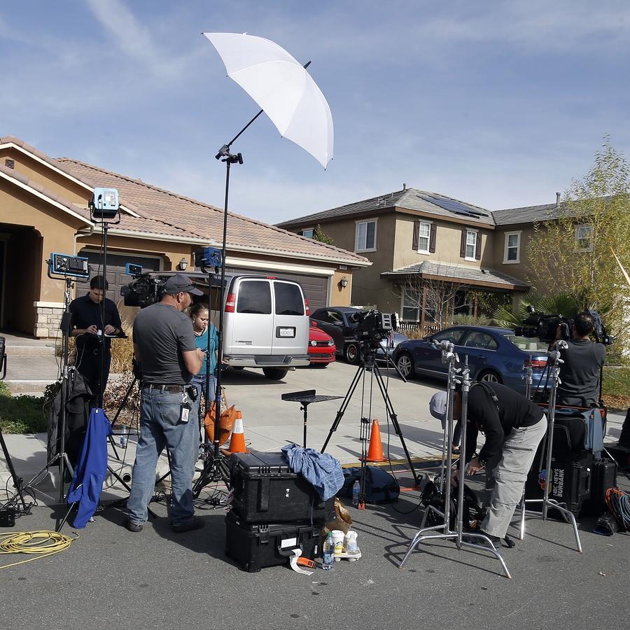 Los medios trabajan fuera de casa donde la policía arrestó el domingo a una pareja acusada de mantener cautivos a 13 niños en Perris, California.