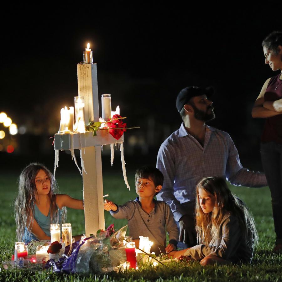 Rich y Rachel Castleberry visitan con sus hijos una de las 17 cruces tras una vigilia por las víctimas de la balacera en la escuela secundaria Marjory Stoneman Douglas.