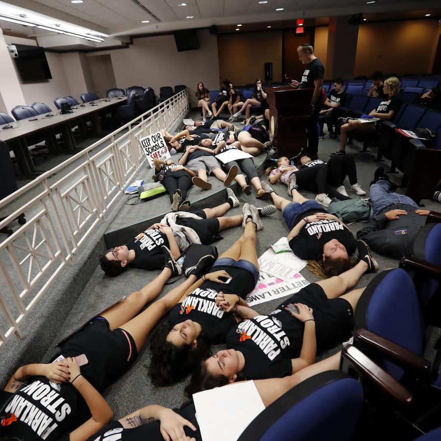 Alumnos supervivientes de la matanza de Parkland yacen en el suelo, rezando, en el Congreso estatal de Florida, una semana después del tiroteo.