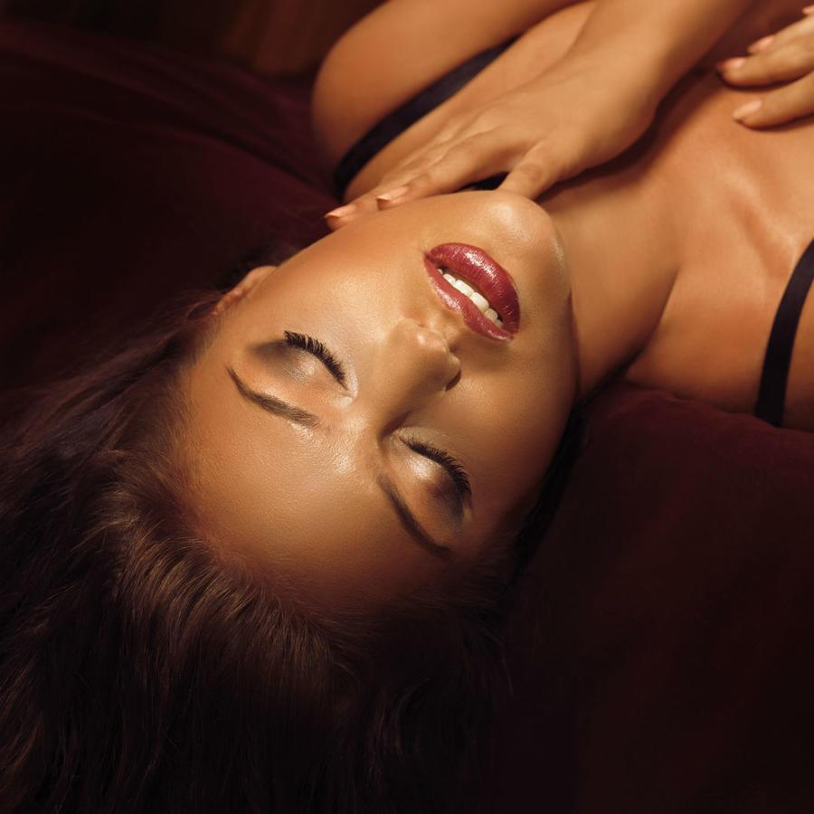 Mujer en lencería recostada sobre la cama