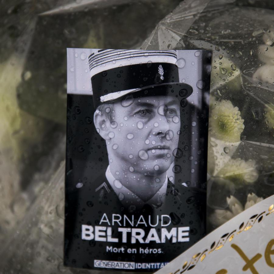 Una foto de  Arnaud Beltrame colocada sobre una homenaje de flores en Carcasona, Francia, este sábado.