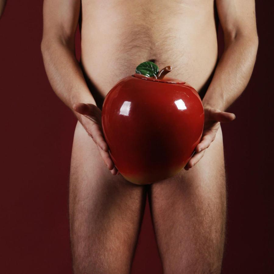 Hombres cubriendo sus genitales con manzanas