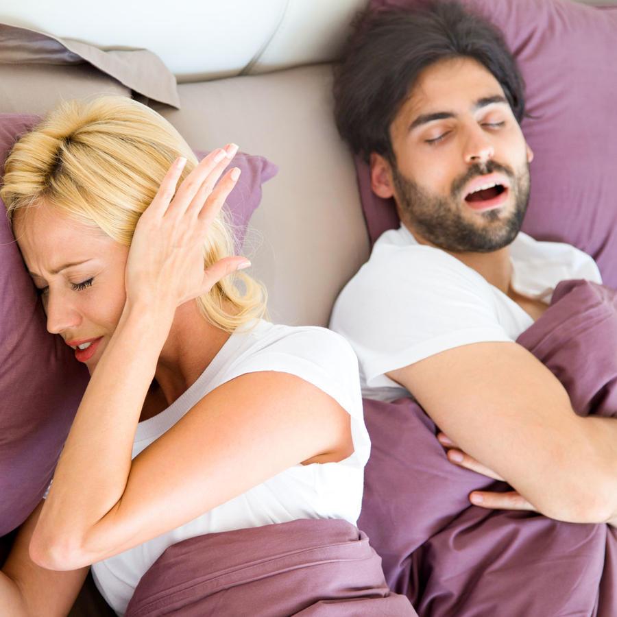 Mujer cubriendo sus orejas, mientras su pareja ronca