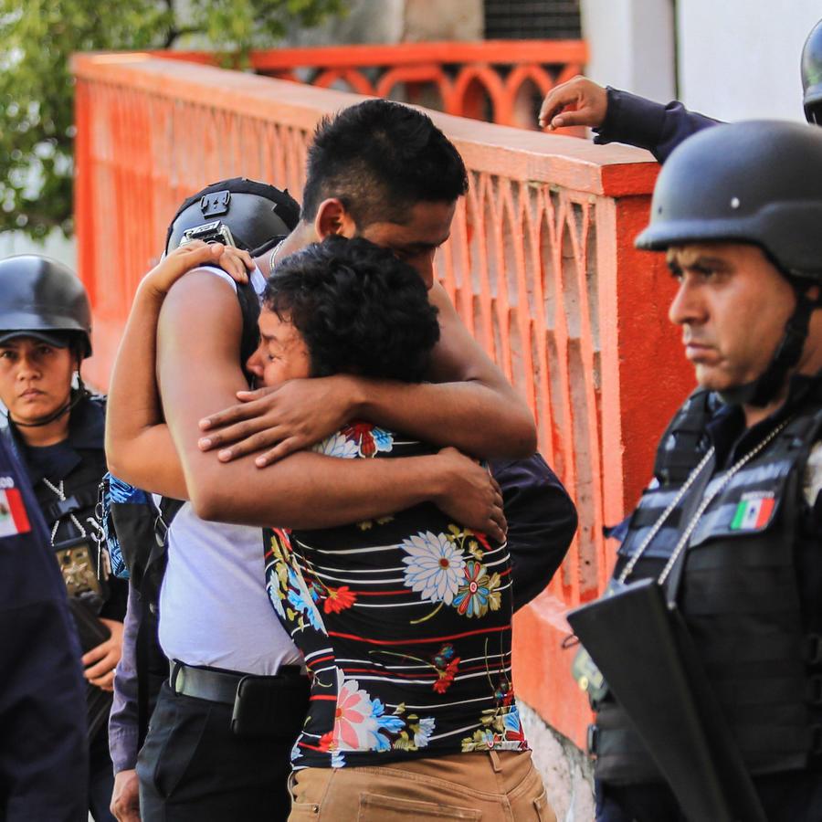 Una pareja se abraza en medio de policías tras el ataque de un grupo armado el 19 de abril de 2018, en Acapulco, Guerrero.