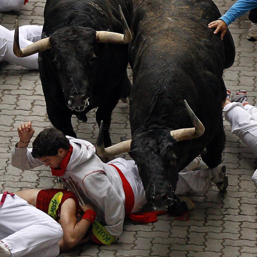 Imagen de archivo de unos jóvenes corriendo frente a los toros durante las fiestas de San Fermín en Pamplona (España).