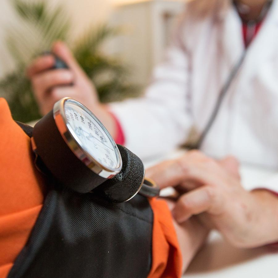 Médico tomando presión arterial de paciente