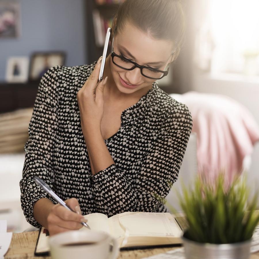 Mujer hablando por teléfono y tomando nota