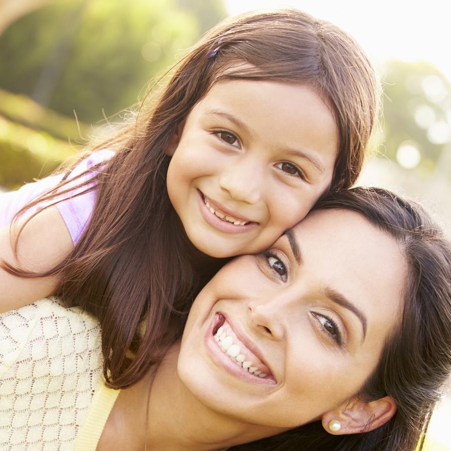 Madre e hija sonriendo al aire libre