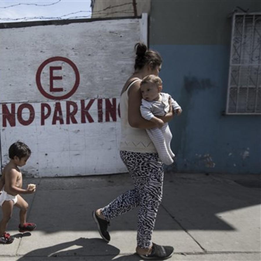 Una madre migrante de Honduras camina con sus hijos hacia un refugio en Tijuana, México.