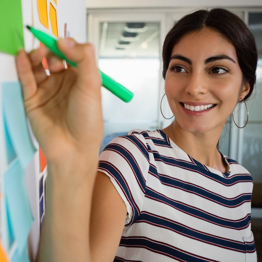 Mujer escribiendo con fibrón en oficina