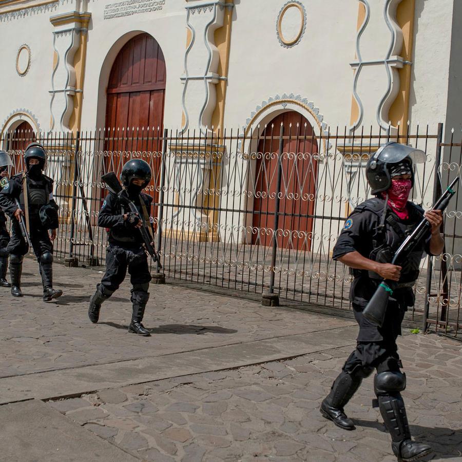 Policías fuertemente armados vigilan la iglesia donde están refugiados estudiantes que protestas contra el gobierno de Daniel Ortega