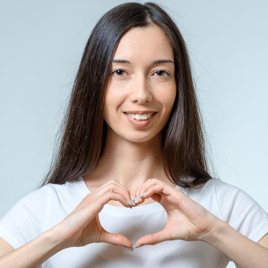 Mujer haciendo forma de corazón con sus manos