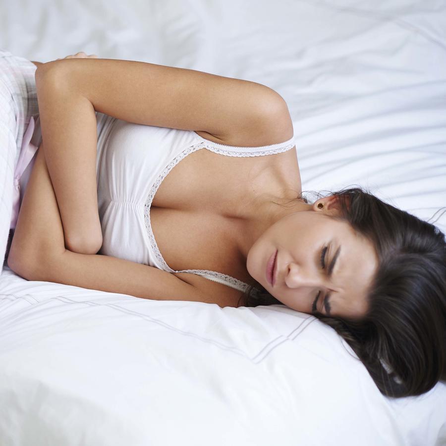 mujer acostada con dolor abdominal