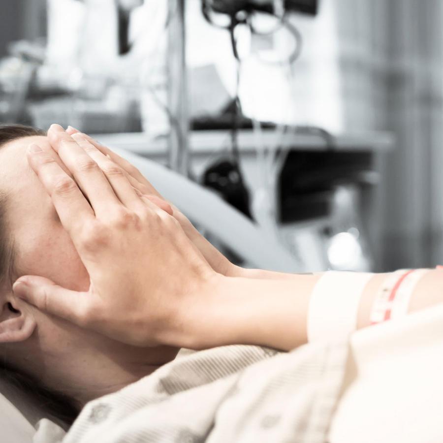Mujer angustiada en cama de hospital