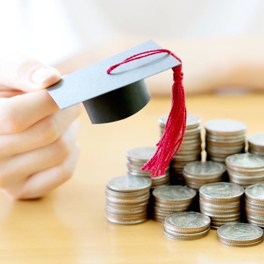 Persona colocando birrete de graduación sobre monedas