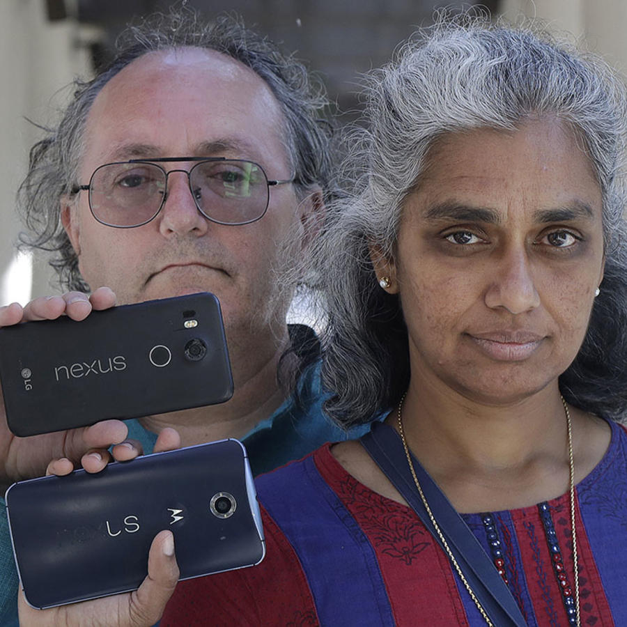 Una pareja sostiene dos celulares que podrían ser vulnerables ante las políticas de ubicación de Google.
