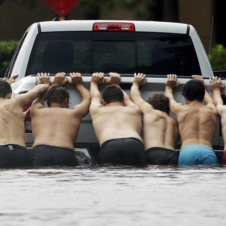 Un grupo de personas empuja una camioneta el 27 de agosto de 2017 en Houston.