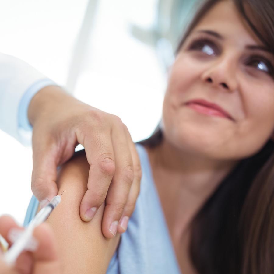 Mujer sonriente recibiendo vacuna