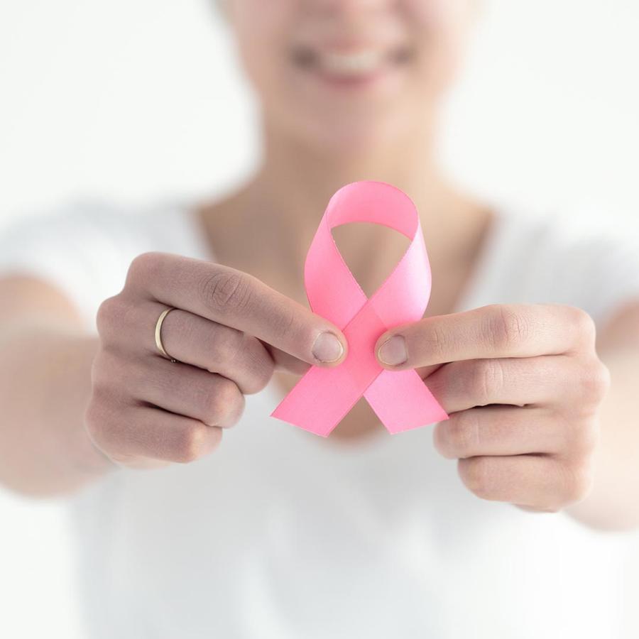 Mujer sosteniendo un listón rosa