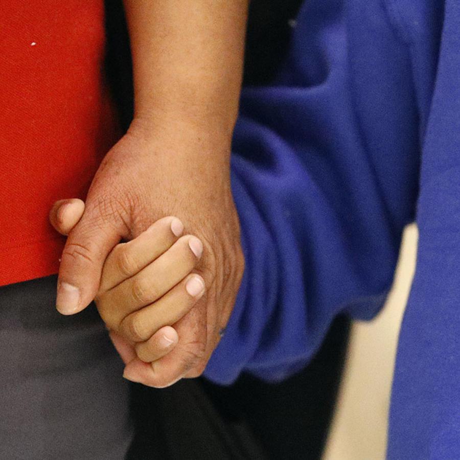 Un niño migrante sostiene la mano de su madre.