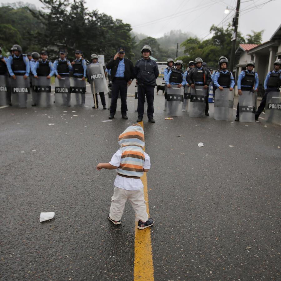 Niño que viaja con la caravana de migrantes frente a policías en Aguacaliente, Honmduras