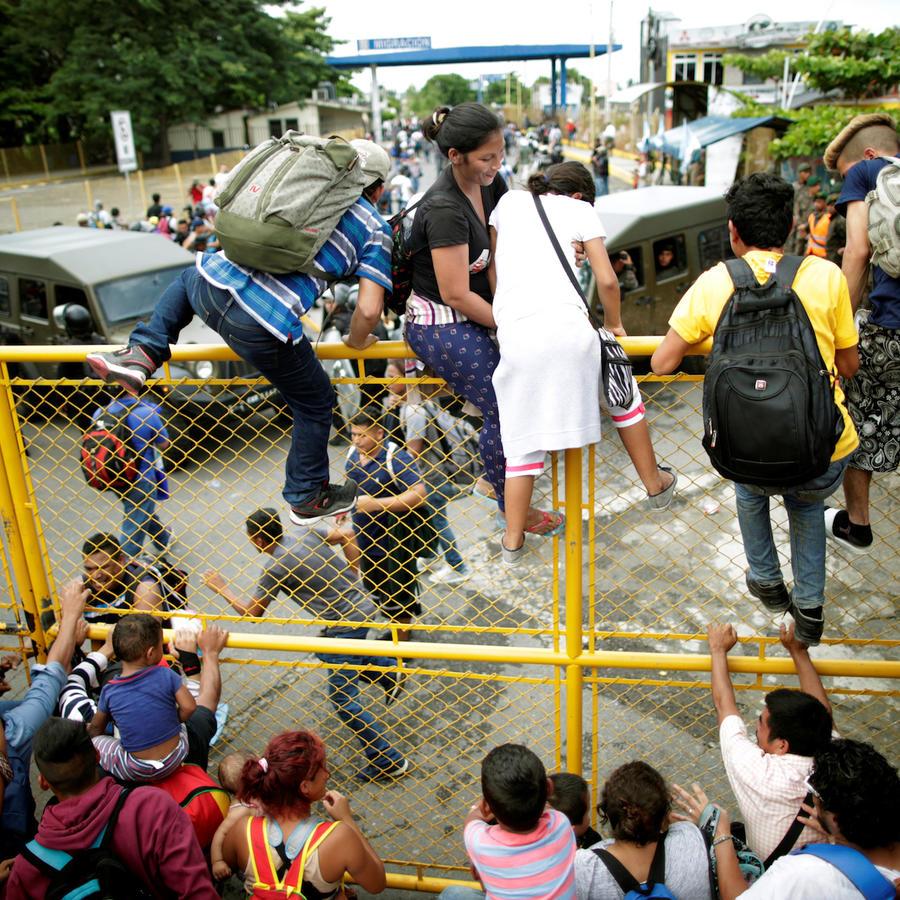 Inmigrantes de la caravana centroamericana salta la verja para entrar en México desde Guatemala.