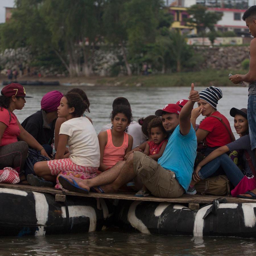 Integrantes de la caravana sobre una barca en el río Sichuate en la frontera entre México y Guatemala