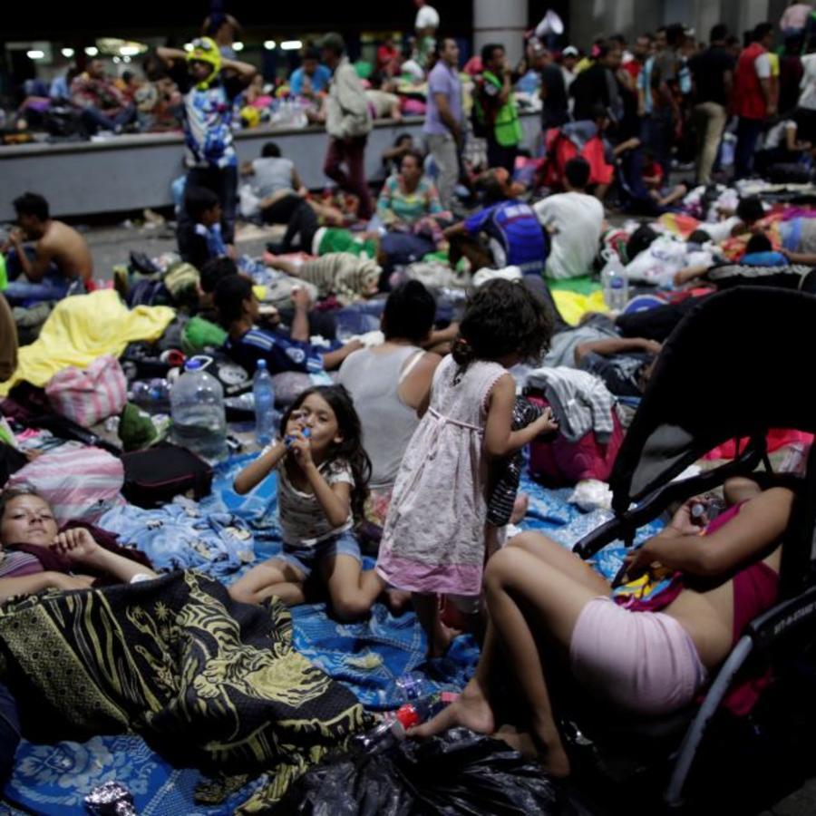 Migrantes descansan este domingo en las aceras del centro de la ciudad de Tapachula, México.