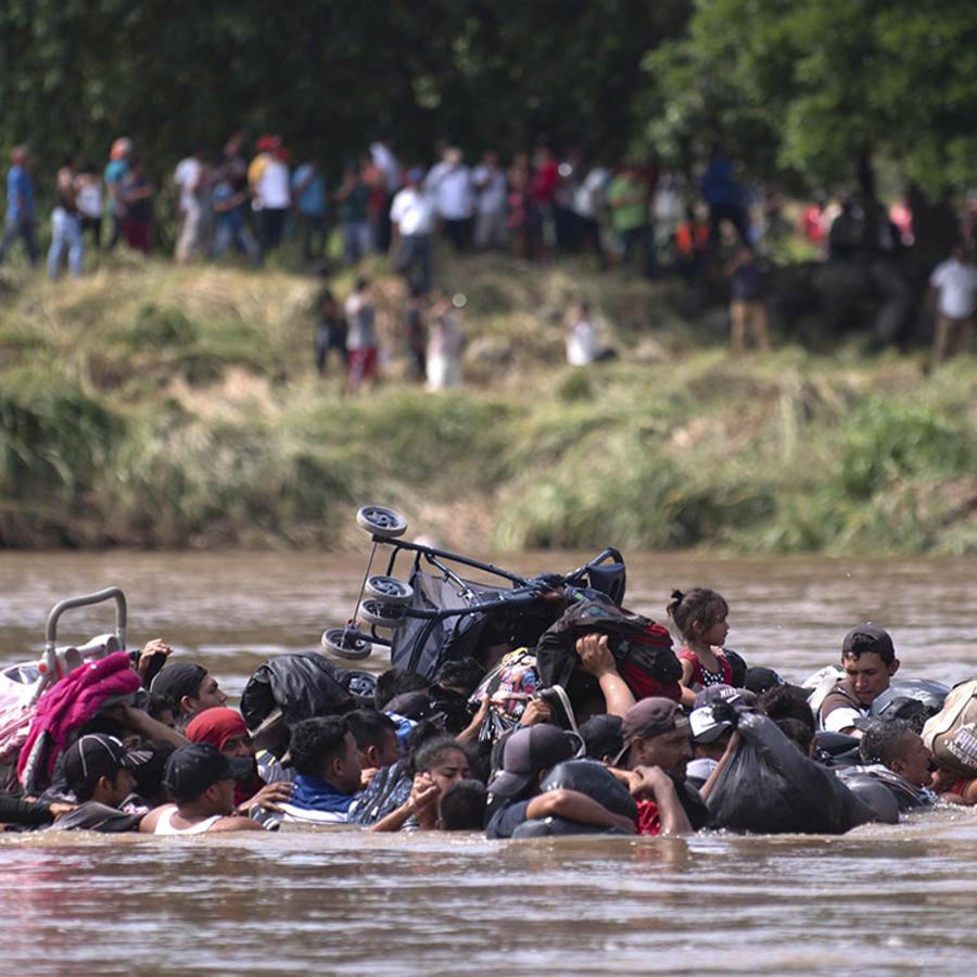 Un grupo de centroamericanos que viaja con la segunda caravana migrante en su intento por cruzar el río Suchiate.