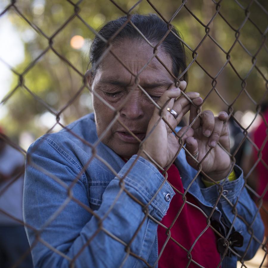 Una mujer de la caravana de migrantes que espera llegar a Estados Unidos reza en un albergue temporal en Tijuana