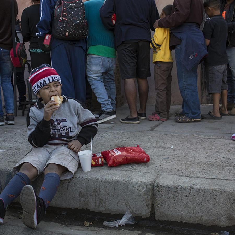 Un niño centroamericano come un pan donado por un refugio provisional en Tijuana, México.